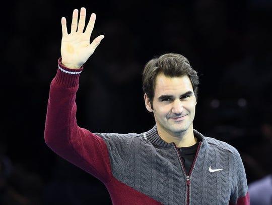 Roger Federer of Switzerland waves as he arrives to