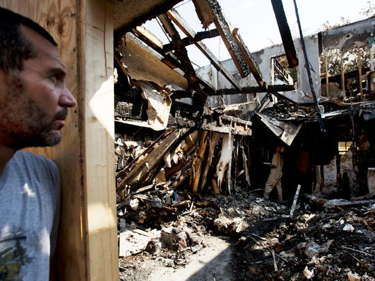 Scott Vanselow surveys the remains of his Fort Myers Beach home as a fire consultant hired by his insurance company begins an investigation. Vanselow and his wife, Kristin, believe the actions of their dog Bella may have saved their lives.