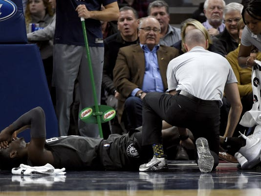 Brooklyn Nets guard Caris LeVert (22), a former Michigan standout, is  tended to after an injury during the second quarter Monday in Minneapolis.