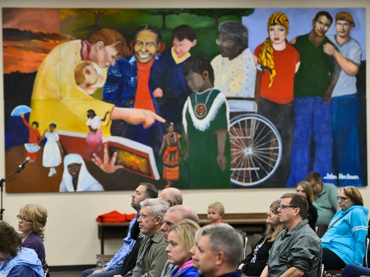 Community members gather under a large mural in the Technical High School media center on Oct. 11 to listen to a presentation on the upcoming referendum to build a new Tech and renovate Apollo High School.