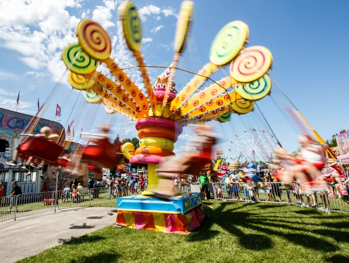 Fair goers spin round on a carnival ride during Sussex