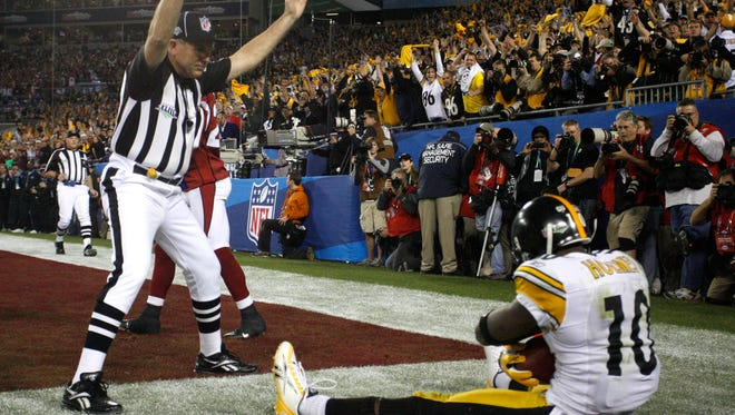 The umpire signals touchdown as Pittsburgh Steelers wide receiver Santonio Holmes (10) sits on the ground after scoring during the fourth quarter of the NFL Super Bowl XLIII football game against the Arizona Cardinals, Sunday, Feb. 1, 2009, in Tampa, Fla. The Steelers won 27-23. (AP Photo/St. Petersburg Times, Brian Cassella)