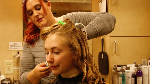 Mid-State Cosmetology student Margaret Weber using REF products during a styling session in the Mid-State Salon, with guest Amelie Riedle.