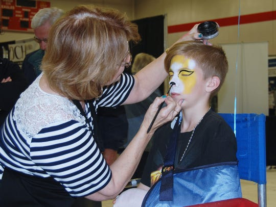 Logan Biles, of Nixa, has his face painted at NIXPO