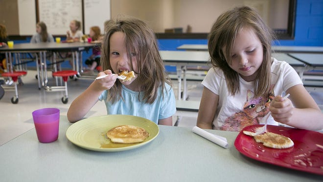 Anaya Cowling 5, left, and her sister Hope Cowling, 7, eat a pancake breakfast at the Plover Boys & Girls Club on Monday, June 29, 2015.