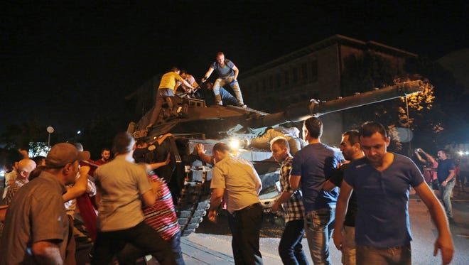 A tank moves into position as Turkish people attempt to stop them, in Ankara, Turkey, late Friday, July 15, 2016. Members of Turkey's armed forces said they had taken control of the country, but Turkish officials said the coup attempt had been repelled early Saturday morning in a night of violence, according to state-run media.