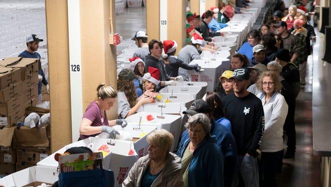 Volunteers help fill Empty Stocking Fund baskets on Dec. 23, 2017.