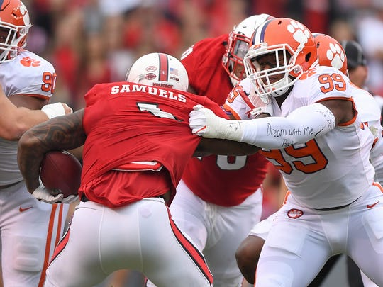 Clemson defensive lineman Clelin Ferrell (99) wraps up NC State's Jaylen Samuels (1) during the 1st quarter on Saturday, Nov. 28, 2017 at Clemson's Memorial Stadium.