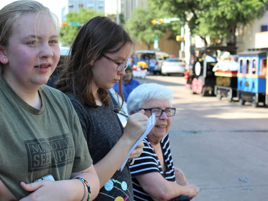 Katherine Strader, 13, center, an eighth-grader from Tyler, makes notes for her story for the Reporter-News about the Children's Art & Literacy Festival's Storybook Parade on Thursday.