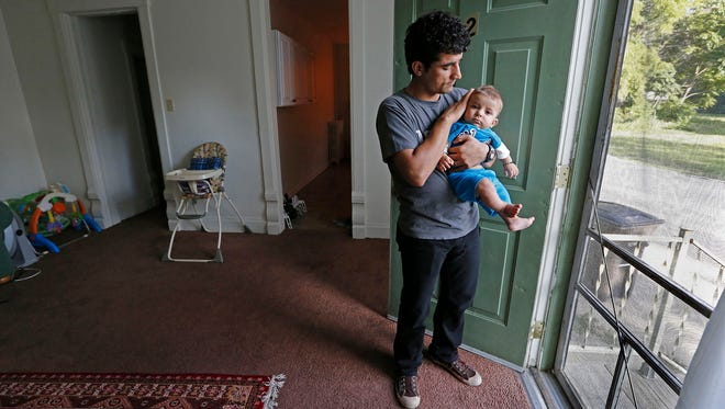 Nabiullah Mohammadi tends to his son, Arman, 4 months, inside his Des Moines apartment. Mohammadi, a former interpreter for American troops in the war in Afghanistan, recently moved his family to Des Moines.