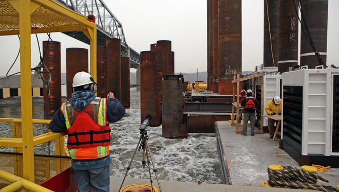 Construction workers use a pile driver Nov. 26, 2013, in the Hudson River in Tarrytown, N.Y. With pile driving for the new Tappan Zee Bridge underway, bubble curtains are used to protect fish from sound waves.