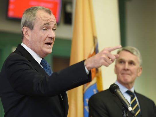 Gov. Phil Murphy speaks to the media as Kevin Corbett,