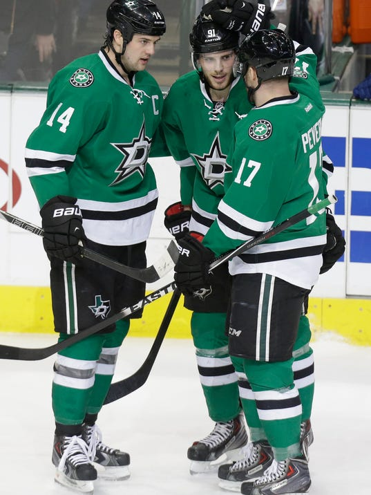 Dallas Stars Tyler Seguin, center, is congratulated by teammates Jamie Benn (14) and Rich Peverley (17) after Seguin scored his second goal against  the Vancouver Canucks during the first period of an NHL hockey game Thursday, March 6, 2014, in Dallas. (AP Photo/LM Otero)