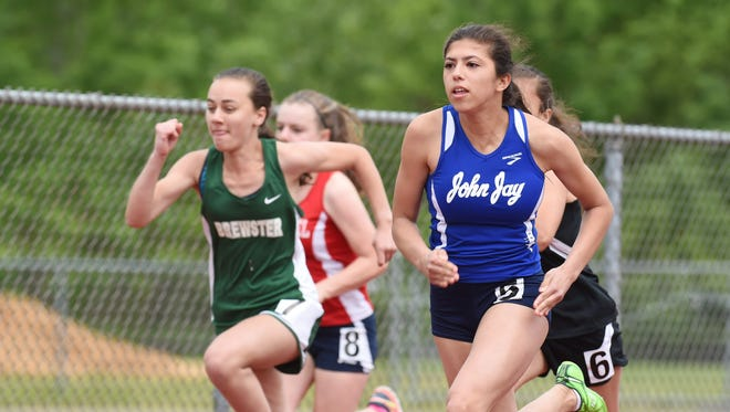 John Jay's Elena Vargas, right, takes the lead during a race at the Northern Counties Championship at Arlington High School in Lagrangeville.