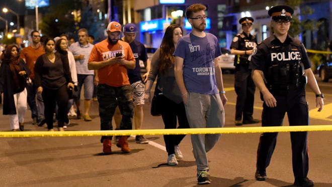 Civilians are escorted from the scene of a shooting in Toronto on Sunday.