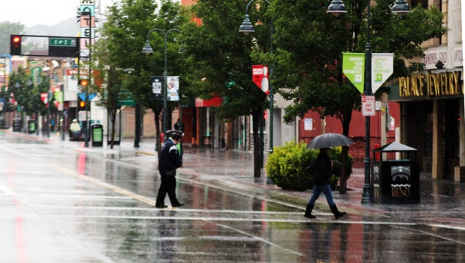 A file photo showing a man and woman crossing North Virginia Street as rain pours down on them in downtown Reno.
