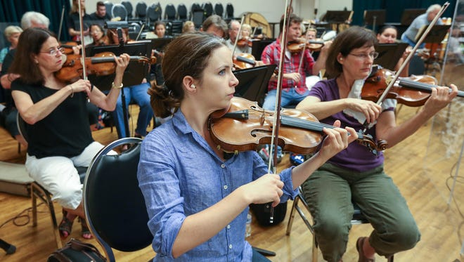 Louisville Orchestra's Cheri Lyon Kelley, first violin, Julia Noone, first violin, and Katheryn S. Ohkubo, first violin, rehearse ahead of a Louisville Ballet performance.September 6, 2016