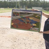 Project chair Laurey Carpenter holds up the plans for the playground where it will be built.