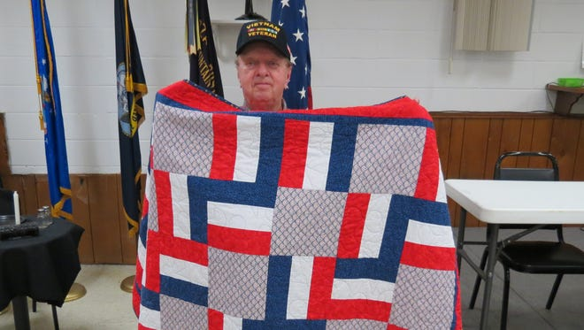 The Mountain Home Quilts Of Valor group made a presentation at Ozark VFW Post 3246 to Army Vietnam veteran Tom Cardwell. Cardwell was honored with a presentation by QOV, Barb Magnuson, Mary Hazel, and Donna Mullaney and received a personalized quilt. These quilts are given to American war veterans with comfort and healing for their military service made by QOV volunteers many are Blue Star mothers. Tom's pastor, veterans, and friends joined in this celebration. The Quilts of Valor started in 2003 by Catherine Roberts whose son was deployed to Iraq. Catherine dream started quilters across this nation to make quilts to honor war veterans. Information for the Mountain Home QOV can be obtained by calling 870) 425-7670.