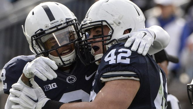 Lions' linebacker Troy Reeder (42) celebrates his interception with teammate Marcus Allen during the homecoming victory against Illinois. Reeder surprised many with his intentions to transfer back home to Delaware.