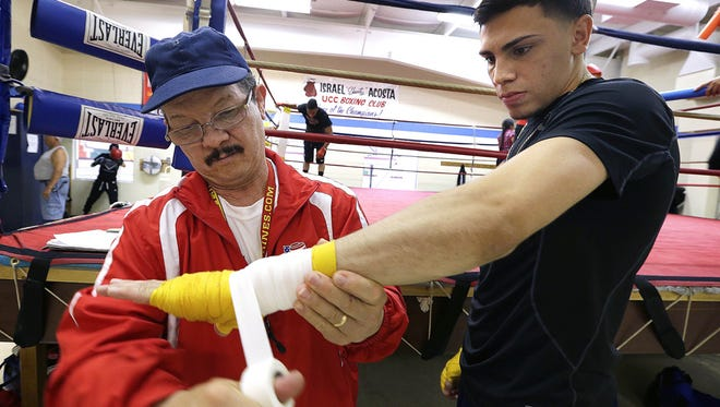 Israel Acosta works with one of his boxers, Luis Feliciano, at the United Community Center in Milwaukee.
