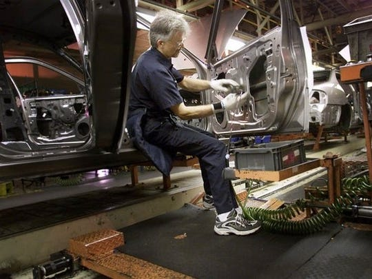 "James Patterson installs a door wiring harness on a Nissan Altima while riding a ""Limo"" to help productivity at the Nissan plant in Smyrna, Tenn. A ""Limo"" helps workers save steps as new cars move down the assembly line."