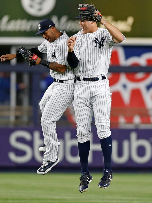 New York Yankees left fielder Aaron Hicks (31) and New York Yankees right fielder Aaron Judge (99) celebrate after the Yankees defeated the Kansas City Royals in a baseball game at Yankee Stadium in New York, Wednesday, May 24, 2017. The Yankees shut out the Royals 3-0. (AP Photo/Kathy Willens)