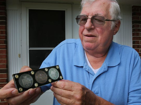 Michael Steinbacher shows off the commemorative coins he was given after a tent collapse on him and others at the first Summerfest.