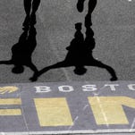 Runners cast shadows as they approach the finish line of the 118th Boston Marathon Monday in Boston.