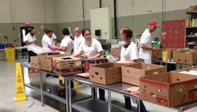 Volunteers from the Clark Construction Group and McCarthy Building Cos. Inc. help process food last year at the El Pasoans Fighting Hunger food bank.