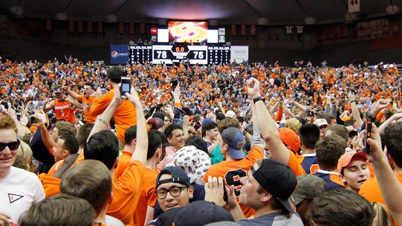 Syracuse fans celebrate on the court after Syracuse defeated Duke in the finals seconds of an NCAA college basketball game in Syracuse, N.Y., Wednesday, Feb. 22, 2017. Syracuse won 78-75. (AP Photo/Nick Lisi) ORG XMIT: NYNL109