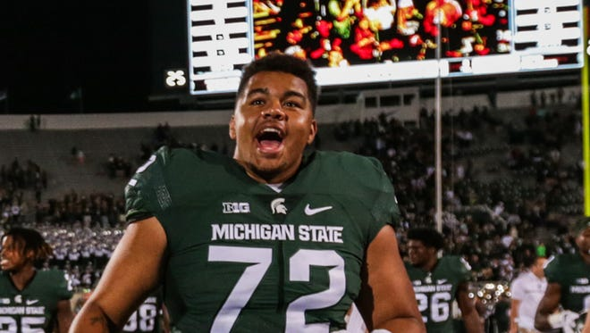 Michigan State Spartans players, including receiver Cam Chambers (21) and offensive lineman Thiyo Lukusa (72)  celebrate after the opening win against Furman at Spartan Stadium in East Lansing, Michigan, on Friday, September 2, 2016.