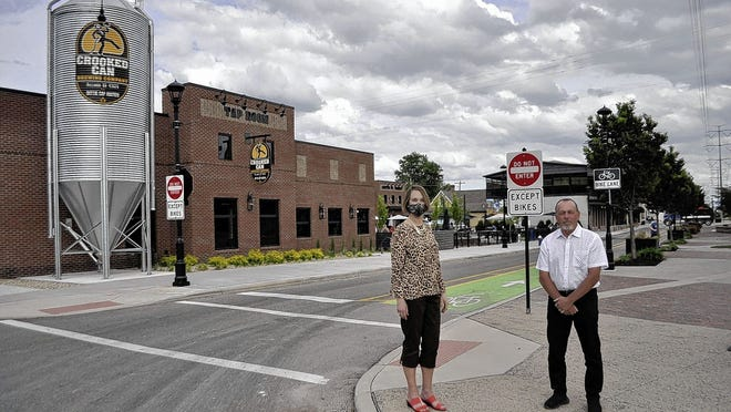 Libby Gierach (left), president and CEO of the Hilliard Area Chamber of Commerce, and Tim Kauffman, executive director of Destination Hilliard, stand at Hilliard's Station Park along Center Street in Old Hilliard. In the background is the new Center Street Market at 5354 Center St., anchored by Crooked Can Brewing Co. The leaders of both organizations said they are working to help revive Hilliard's restaurants and businesses in the wake of shutdowns during the COVID-19 coronavirus pandemic.