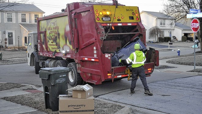 Local Waste Services workers empty waste containers in Hilliard last year. The city of Whitehall is considering whether a new five-year deal with the company for trash and recycling collection should include uniform containers for residents.