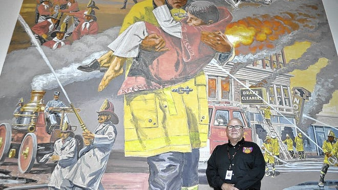 Hilliard resident Kevin Reardon was appointed by Gov. Mike DeWine as Ohio's 39th state fire marshal. He is standing by a mural depicting firefighters at the Ohio Department of Commerce's Division of State Fire Marshal office, 8895 E. Main St. in Reynoldsburg.