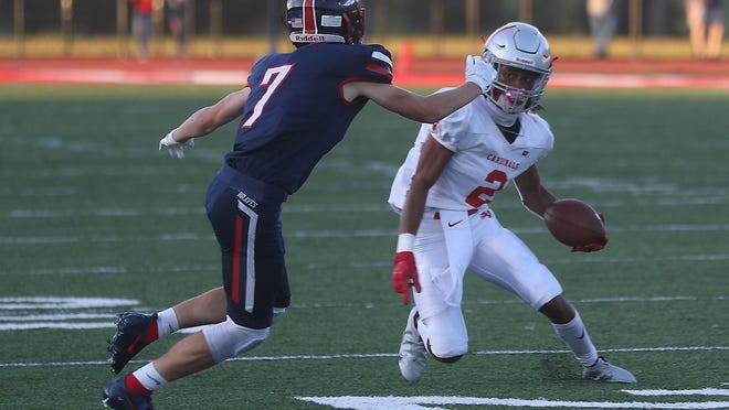 Sandy Valley receiver Demetrius Evans tries to avoid an Indian Valley defender during  a game against the Braves earlier this season. Evans now holds the Cardinals' career receiving yards record with 2,082.