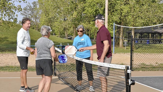 Pickleball players (from left) Tony Allen, 64, Sharon Laut, 77, Elaine Howett, 76, and Jeff Clark, 71, all Hilliard residents and members of the Phyllis A. Ernst Senior Center, give a paddle bump at the conclusion of a match Sept. 16 on the new courts in Roger A. Reynolds Municipal Park in Hilliard.
