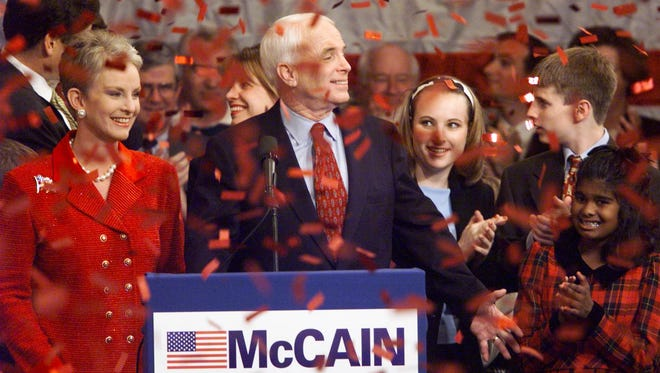 Republican presidential hopeful Arizona Sen. John McCain celebrates with his wife Cindy (left) following his victory speech in 2000 at the Pointe Hilton Squaw Peak in Phoenix.