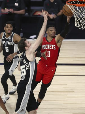 Houston Rockets guard Russell Westbrook (0) goes up for a shot past San Antonio Spurs center Jakob Poeltl (25) during the first half of an NBA basketball game Tuesday in Lake Buena Vista, Fla.