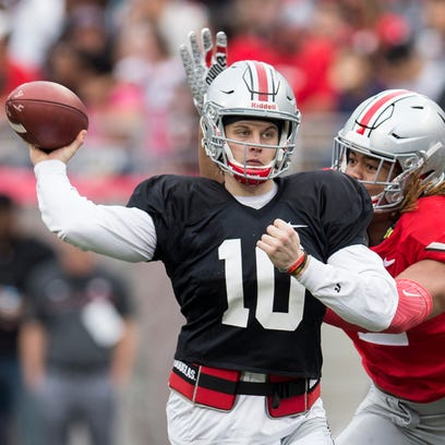 Joe Burrow throws a pass under pressure from Chase