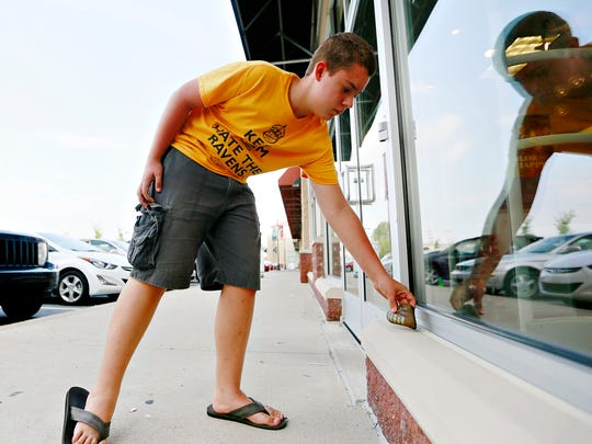 Richard Kessler, 13, of East Manchester Township, places a kindness rock at a shopping center in Springettsbury Township, Monday, Aug. 21, 2017. Dawn J. Sagert photo
