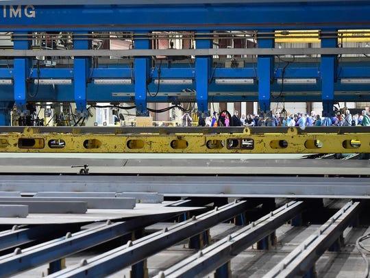 A group touring Fincantieri Bay Shipbuilding can be seen through an IMG panel line welding machine.