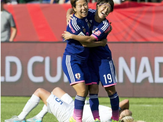 Japan's Azusa Iwashimizu and Saori Ariyoshi (19) celebrate the team's 2-1 win as England's Steph Houghton lies on the ground Wednesday's Women's World Cup semifinal in Edmonton, Alberta. England scored an own goal during stoppage time to give Japan a 2-1 win. Japan will play the United States in Sunday's championship match.
