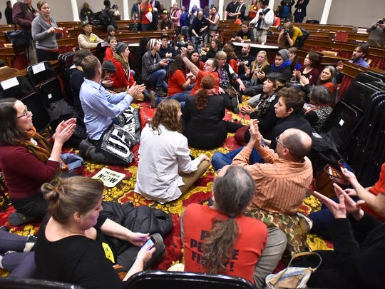 Single-payer protesters sit down in the well of the House chamber after Gov. Peter Shumlin's inauguration ceremony at the Statehouse in Montpelier on Thursday, January 8, 2015.
