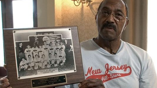 Otha Crowder holds a photo that shows his Hammonton Little League All-Star team that won the Little League World Series in 1949.