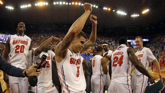 Florida Gators guard Scottie Wilbekin (5), Florida Gators guard Michael Frazier II (20) and teammates celebrate after they beat the Kentucky Wildcats during the second half at Stephen C. O'Connell Center.