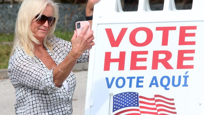 Cindy Carol, after casting her vote, takes a selfie with the Vote Here sign, Tuesday November 6, 2018 at City Island Library in Daytona Beach.