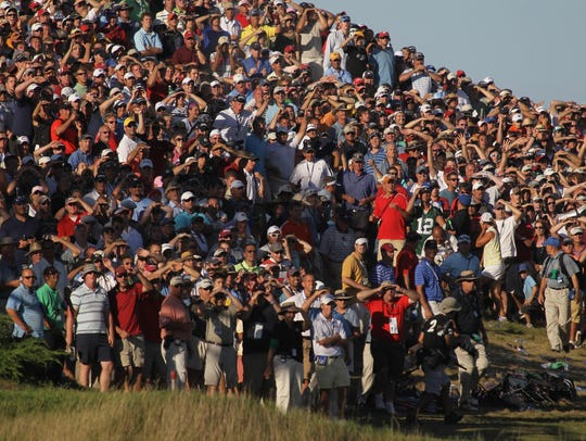 Dustin Johnson is hidden by the crowd as they cheer