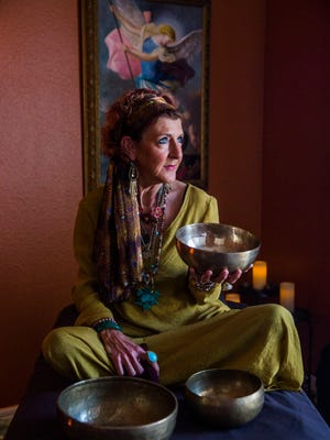 Bindi Shoulders, 50, offers holistic healing sessions, including Tibetan Bowl Sacred Sound Therapy. Shoulders sits for a portrait with one of the bowls used for the therapy in her Cape Coral home on Friday, April 7, 2017.