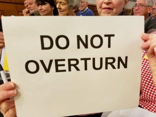 A supporter of upholding the landmark designation holds